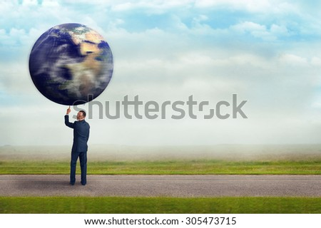 businessman holding spinning planet earth aloft with one finger subtle vintage filter and selective focus with copy space