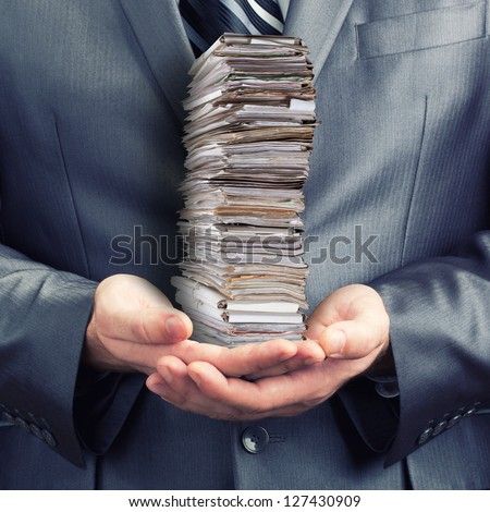 Businessman holding stack of documents - stock photo