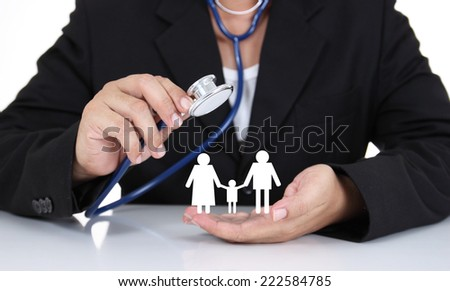 Businessman holding stethoscope with paper family - stock photo