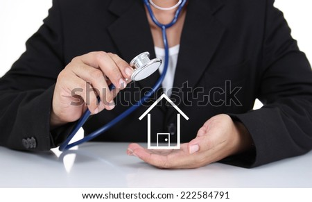 Businessman holding stethoscope with paper house - stock photo