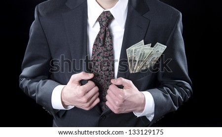 Businessman holding suit lapels with twenty dollars bills in his jacket pocket - stock photo