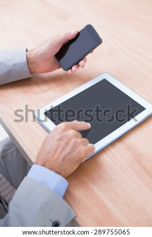 Businessman holding tablet and smartphone in his office