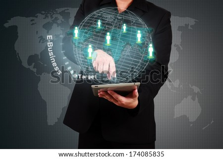 Businessman holding tablet and touching a target on virtual screen. E-business concept.