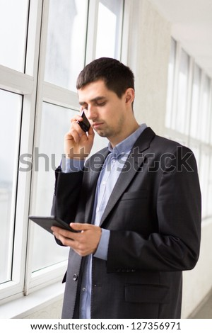 Businessman holding tablet pc and works on it - stock photo