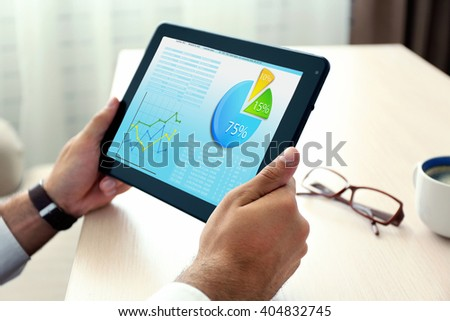 Businessman holding tablet-pc with scheme on screen