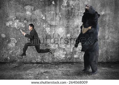 Businessman holding tablet running from an angry bear with gray mottled concrete wall and floor background - stock photo