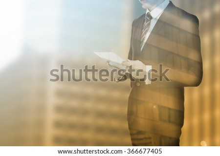 Businessman holding tablet with double exposure - stock photo