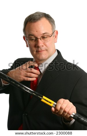 Businessman holding tennis racket and removing tie - stock photo