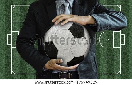 Businessman holding the ball on a black background. - stock photo