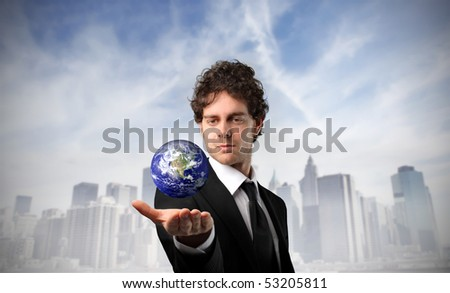 Businessman holding the earth in his hand with cityscape on the background - stock photo