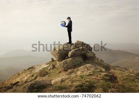 Businessman holding the Earth in his hands on a rock in the mountains - stock photo