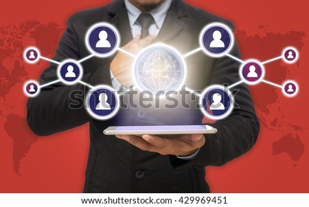 Businessman holding the tablet with the Social media symbol on red color background with world map, Elements of this image furnished by NASA, Business network concept