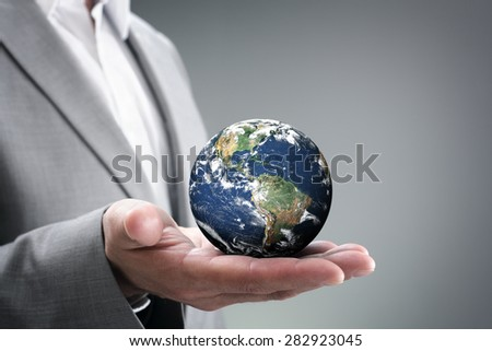 Businessman holding the world in the palm of hands concept for global business, communications, politics or environmental conservation  Earth image courtesy of Nasa   - stock photo