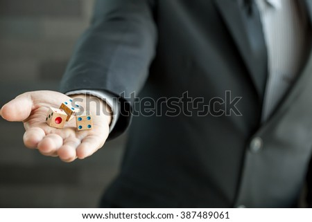 Businessman holding three dices - stock photo