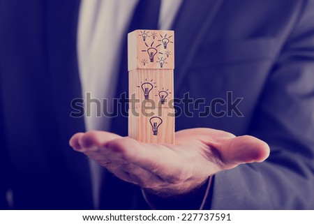 Businessman holding three wooden cubes vertically aligned, with hand-drawn incandescent light bulbs, concept of creative ideas and new business projects. - stock photo