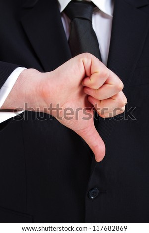 Businessman holding thumbs down - stock photo