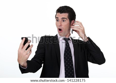 businessman holding two cell phones - stock photo