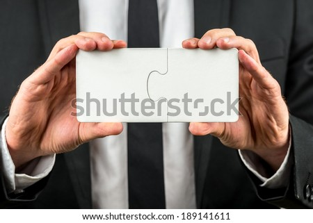 Businessman holding two interlocked blank white jigsaw puzzle pieces in his hand depicting the completion of a deal, solution to a problem or overcoming a challenge. - stock photo