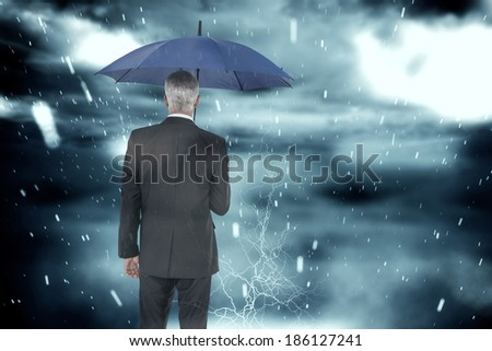 Businessman holding umbrella against cloudy sky with snow falling