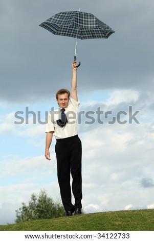 businessman holding umbrella over head - stock photo