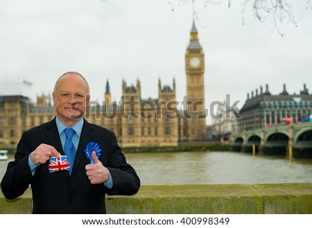 Businessman holding Union Jack purse in front of the Houses Of Parliament in London. - stock photo