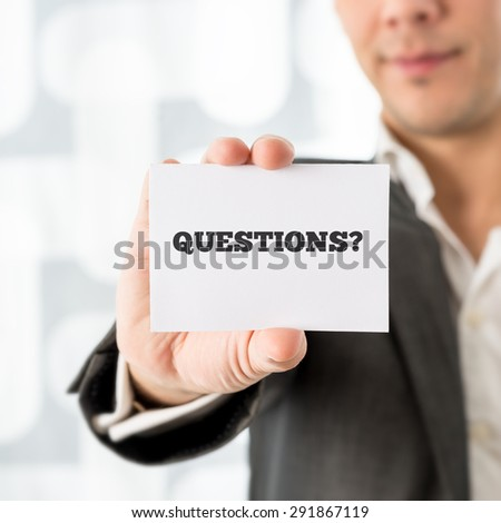 Businessman holding up a small white card saying Questions in a conceptual image of customer support and client services, close up of his hand. - stock photo
