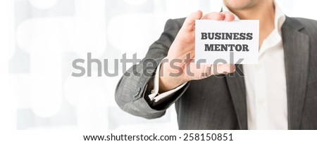 Businessman holding up a small white card with the words Business Mentor in a concept of consulting, advice, skill and experience. - stock photo