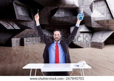 Businessman holding up reading glasses and calculator against abstract room - stock photo