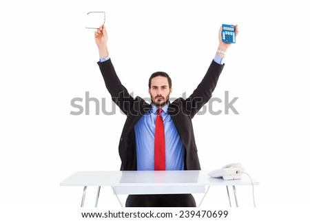 Businessman holding up reading glasses and calculator on white background - stock photo