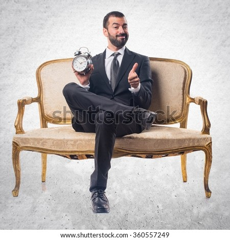 Businessman holding vintage clock - stock photo