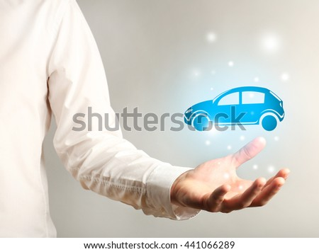 Businessman holding virtual car on grey background