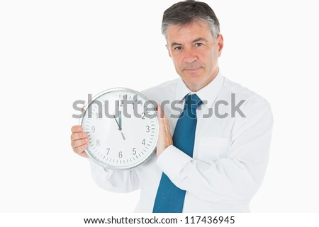 Businessman holding wall clock