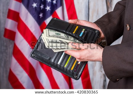 Businessman holding wallet with dollars. American flag, wallet and money. Salary came just in time. Labor, wealth and patriotism. - stock photo