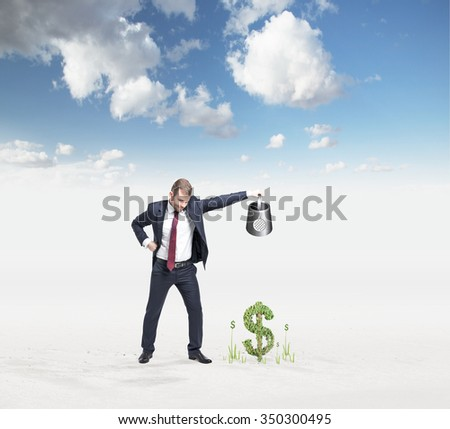 businessman holding watering can pouring water on money so that it grows, blue sky at the background, concept of money accumulation