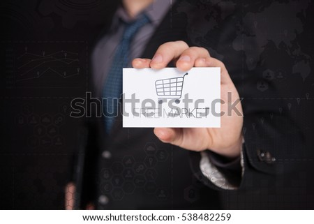 Businessman Holding White Visit Card With Icon And Text Free Market, Touch Screen. Virtual Icon. Graphs Interface. Business concept. Internet concept. Digital Interfaces