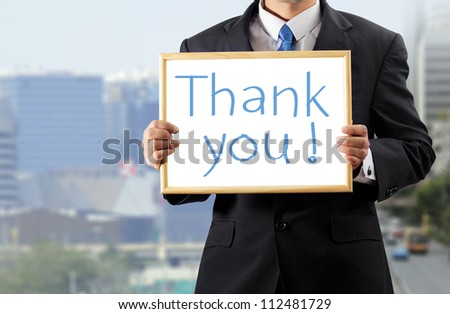 Businessman holding whiteboard with a message thank you. - stock photo