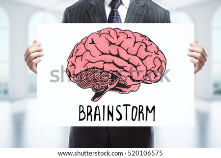 Businessman holding whiteboard with human brain sketch. Brainstorming concept