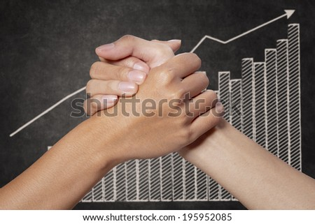 Businessman holding woman hands with growth graph on blackboard - stock photo