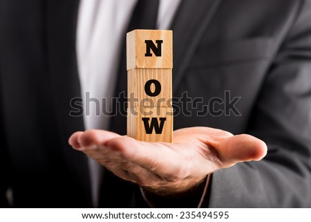 Businessman holding wooden alphabet blocks reading - Now - balanced in the palm of his hand. - stock photo