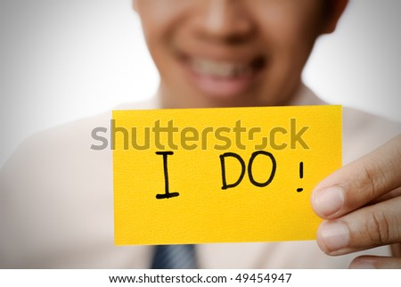 Businessman holding yellow card showing words ?V I do. - stock photo