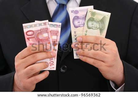 businessman holding yuan and euro in his hands - stock photo