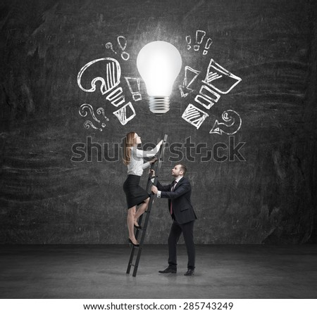 Businessman holds a ladder for business lady who is climbing up. The concept of the teamwork and cooperation. - stock photo