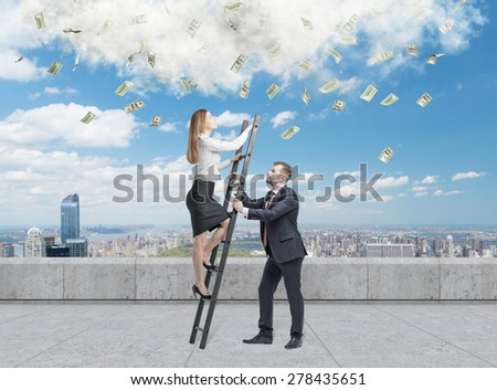 Businessman holds a ladder for the business lady. The concept of the teamwork. On the roof terrace in Manhattan. Dollar notes falling from the sky. - stock photo