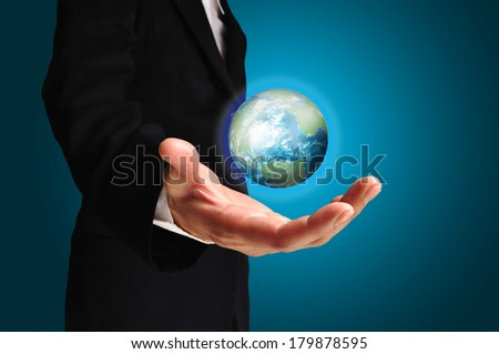 Businessman holds Earth in a hand. Elements of this image furnished by NASA  - stock photo