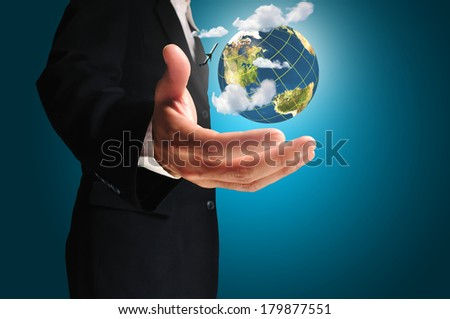 Businessman holds Earth in a hand with airplane and cloud.  Elements of this image furnished by NASA