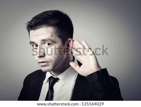 Businessman holds his hand near his ear and listening something - stock photo