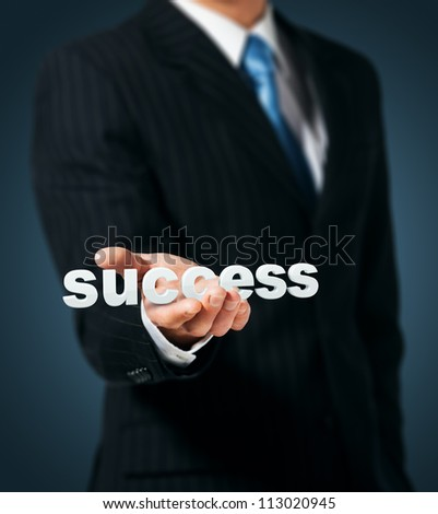 Businessman holds in a hand a word success - stock photo