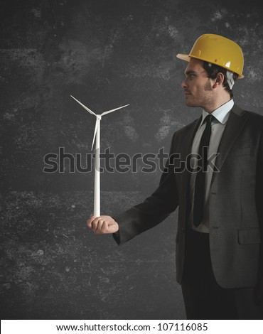Businessman holds in hand a wind turbine - stock photo