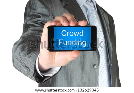 Businessman holds smart phone with crowd funding words on its screen isolated on white background. - stock photo
