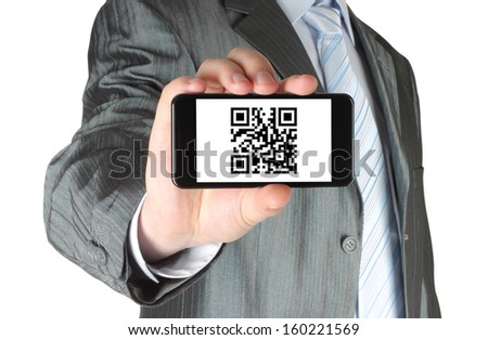Businessman holds smart phone with QR code on white background  - stock photo